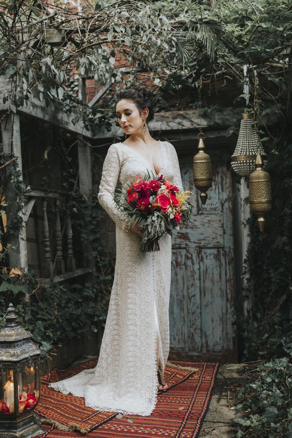 Boho-Braut im langen Spitzenkleid mit Brautstrauß für die Hochzeit im Orient-Trend auf Brautsalat